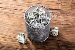 Image of money in a trash can